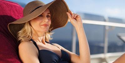 Kvinne med solhatt i solstol på dekk på Cunard-skip.
