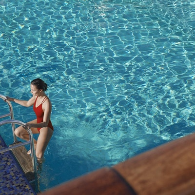 Kvinne i rød badedrakt stiger opp av basseng.