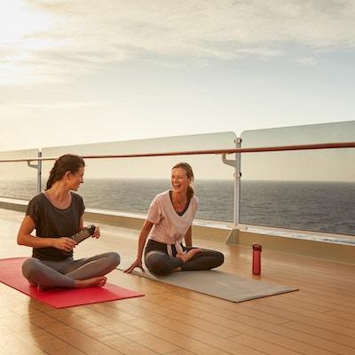 To kvinner på dekk på cruiseskip med yogamatte.