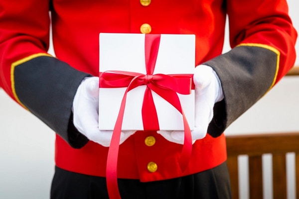 Bell boy holder en gave med rød sløyfe.