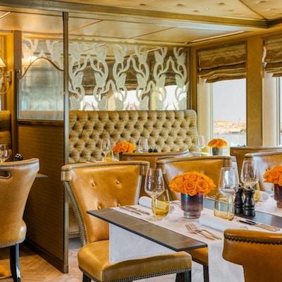 Interiør i brunt og oransje om bord i elvecruiseskip med Venezia i bakgrunnen.