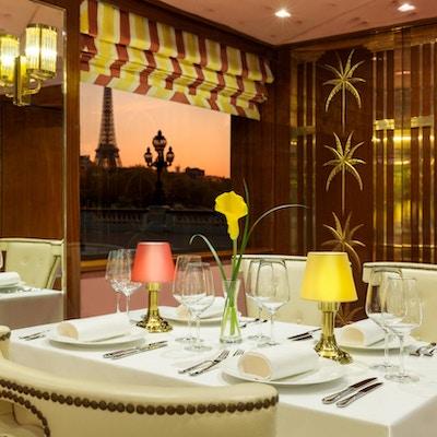 Dekket bord i restaurant med Eiffeltårnet i Paris i bakgrunnen.