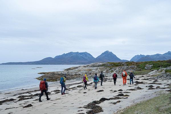 Mennesker på tur langs en strand.