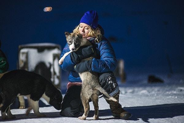 En kvinne som holder en ung hund