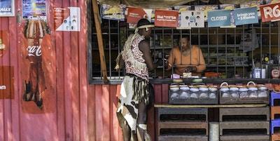 Johannesburg, Sør-Afrika - 24. september 2013: Afrikansk zulu-mann kledd i sin tradisjonelle klær, handlet på en spaza-butikk i Orlando, Soweto. Butikken er laget av en gammel fraktbeholder med skilt og plakater festet på seg. Den er innbruddssikker for sikkerhets skyld.