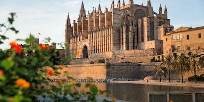 En stor katedral med gotiske spir som ligger ved vannet blomster i forgrunn og palmer