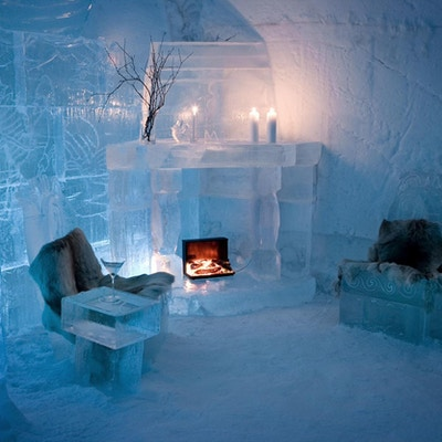 Rom i ishotell med peis, bord og stoler laget av is