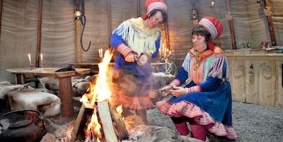 To samekvinner i kofte koker kaffe på bålet i lavvoen