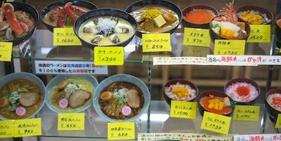 Mat presentert i menyvinduet, ved inngangen til fiskemarkedet, som for øyeblikket tilbys. Maten er plast, flaggermus den ser ut som den ekte, og hver og en har skilt med navn og pris. Dette er en tradisjonell måte å presentere tilberedt mat i Japan på.