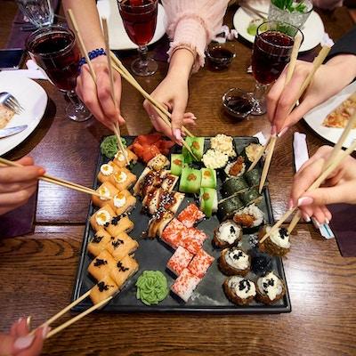 Et sett med sushiruller på et bord i en restaurant. Venner som spiser sushiruller med bambuspinner.