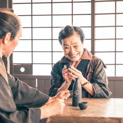 Retro vekkelsesbilde av en gammel kvinne og en gammel mann iført kimono i et tradisjonelt japansk hus. Kvinnen serverer skyld til husbåndet sitt mens
