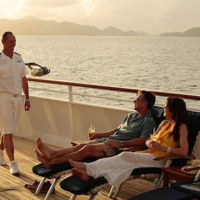 Par på dekk på yacht med drinker, en ansatt kommer smilende forbi.