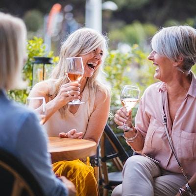 Tre kvinner ler og skåler i rosévin