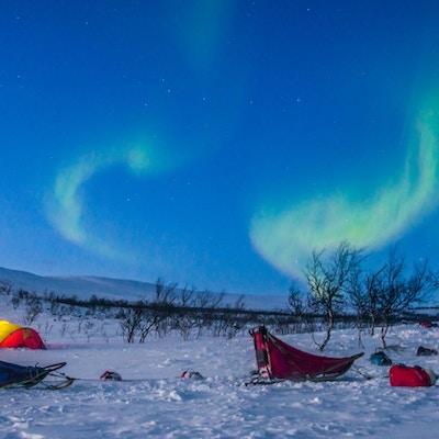 Telt i snø med lys og mektig himmel med nordlys over.