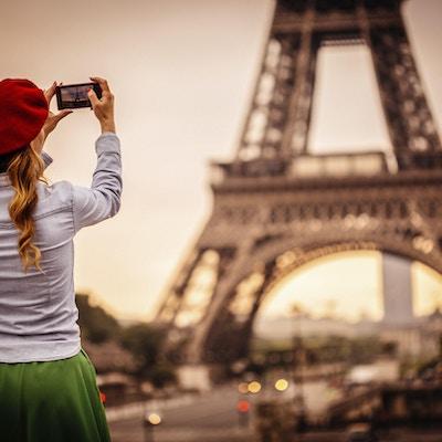 En kvinne som tar bildet av Eiffeltårnet