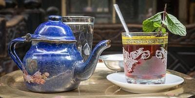 Blå tekanne og glass med te på et brett.