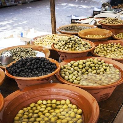 Ulike marinerte oliven og lokal mat på gatemarkedet på Mallorca, Spania. Selger og kjøper.