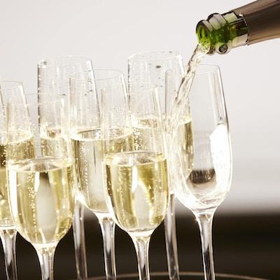 Champagne som helles på et brett.