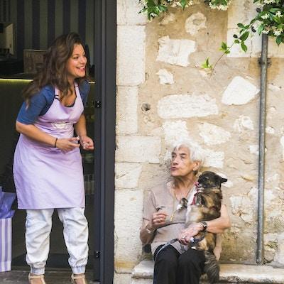 En moden kvinne, som holder kjæledyrhunden sin, sitter på en lav steinbenk mens hun deler en humoristisk samtale med en ung kvinne utenfor butikken hennes i St. Paul de vence, Frankrike.