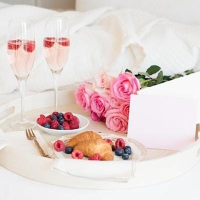 Flat lag med blomster og mat på brett på en seng