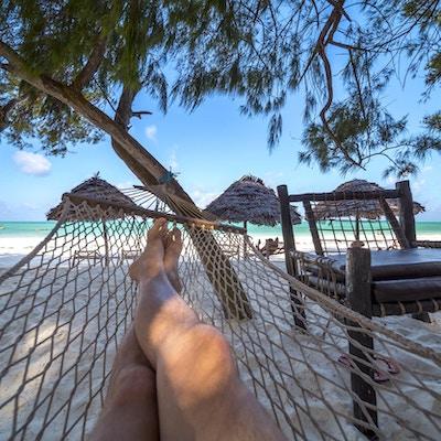 Mannens korslagte ben i hengekøye over den tropiske lagunen