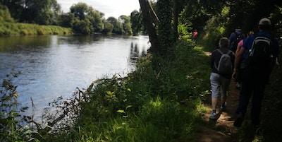 Vandrere på en sti langs en elv fotografert bakfra.