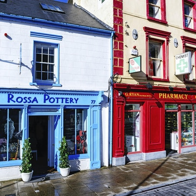 Butikker på Main Street i sentrum av Cashel, Tipperary, Irland. Rossa Pottery og Ryan og Kennedys Apotek. Fargerike gamle forretningsbygg. Ingen folk.