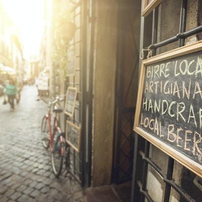 Et skilt som reklamerer for mat langs gaten i solskinn