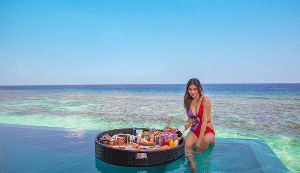 Kvinne på kanten av evighetsbasseng med havet i bakgrunnen og stort frokostbrett flytende i bassenget.