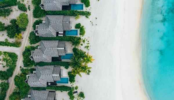 Luftfoto av strandvillaer på rekke ved hvit sandstand og turkist hav.