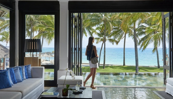 Hotellobby med dame som ser utover havet og stranda med palmer.