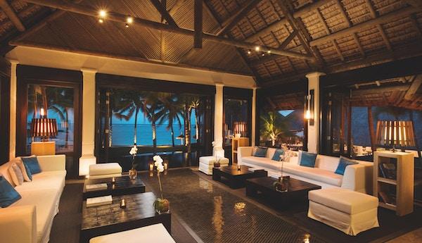 Elegant hotellobby med dempet belysning og hav og palmer utenfor.