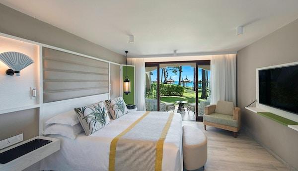 Hotellrom med utsikt mot hage og hav.