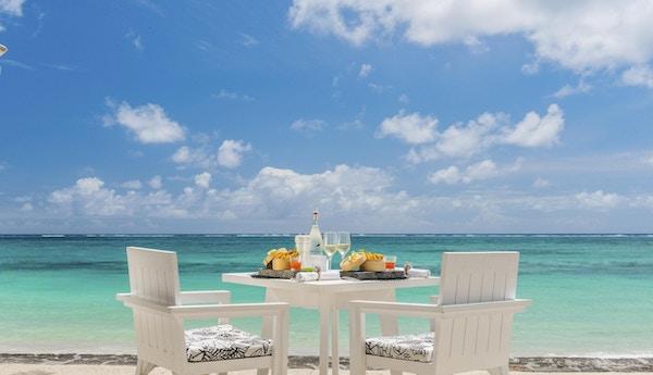 Dekket bord for to på hvit strand med hav og himmel.