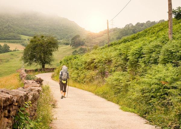 Pilegrim med ryggsekk som går Camino de Santiago i Spania.