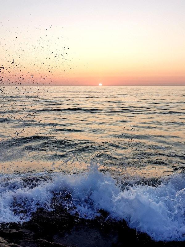 Solnedgang i horisonten med bølge i forgrunnen.