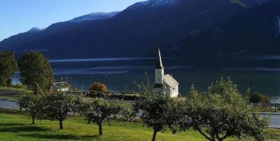 Kirke ved fjorden med frukttrær foran og fjell bak.