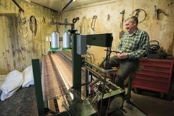 Harris Tweed produseres for hånd etter gammel oppskrift. En mann som jobber på sin fotdrevne vevstol.