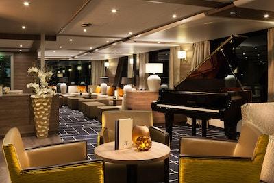 Bar med stoler og piano på elvecruiseskip