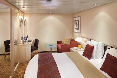 Lugar på cruiseskip med seng og sittegruppe. Foto
