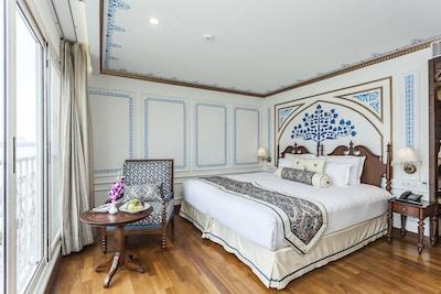 Lugar med tregulv, dekorerte vegger, dobbeltseng, stol, bord og vindu. Foto.