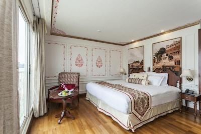 Lugar med tregulv, dobbeltseng, dekorerte vegger, stol, bord og stort vindu. Foto.