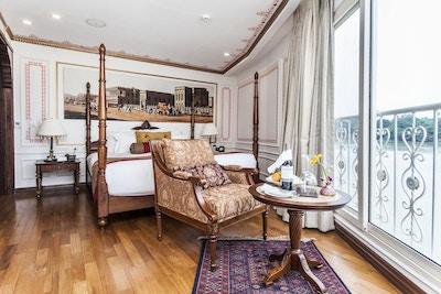 Lugar med dobbeltseng, stol, bord og fransk balkong. Foto.