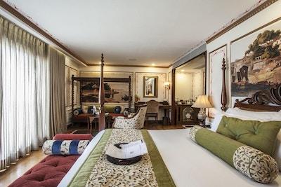 Suite med dekorerte vegger, dobbelseng, sittebenk, dagseng, skrivebord og store vinduer. Foto.