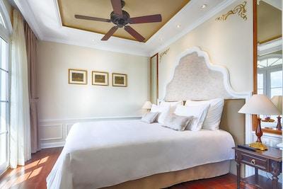 Lugar med tregulv, dobbeltseng, takvifte og nattbord. Foto.