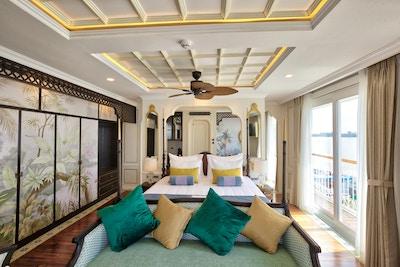 Suite med seng, sofa, puter, vinduer, dekorative vegger, taklampe og fransk balkong. Foto.