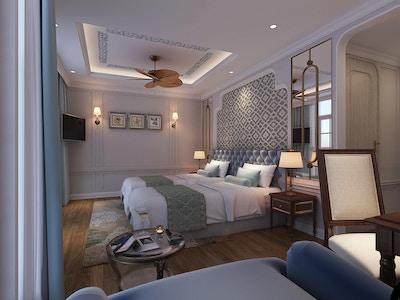 Lugar med to senger, tregulv, takvifte og møbler. Foto.
