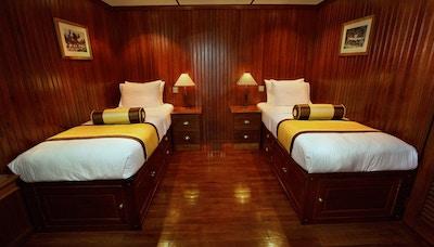Teaklugar med to senger, nattbord og taklamper. Foto.