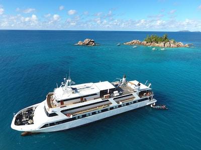 Motoryacht på vannet med øy og båter i bakgrunnen. Foto.
