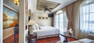 Suite med tregulv, dobbeltseng, sofa, lamper, takvifte og store vinduer. Foto.